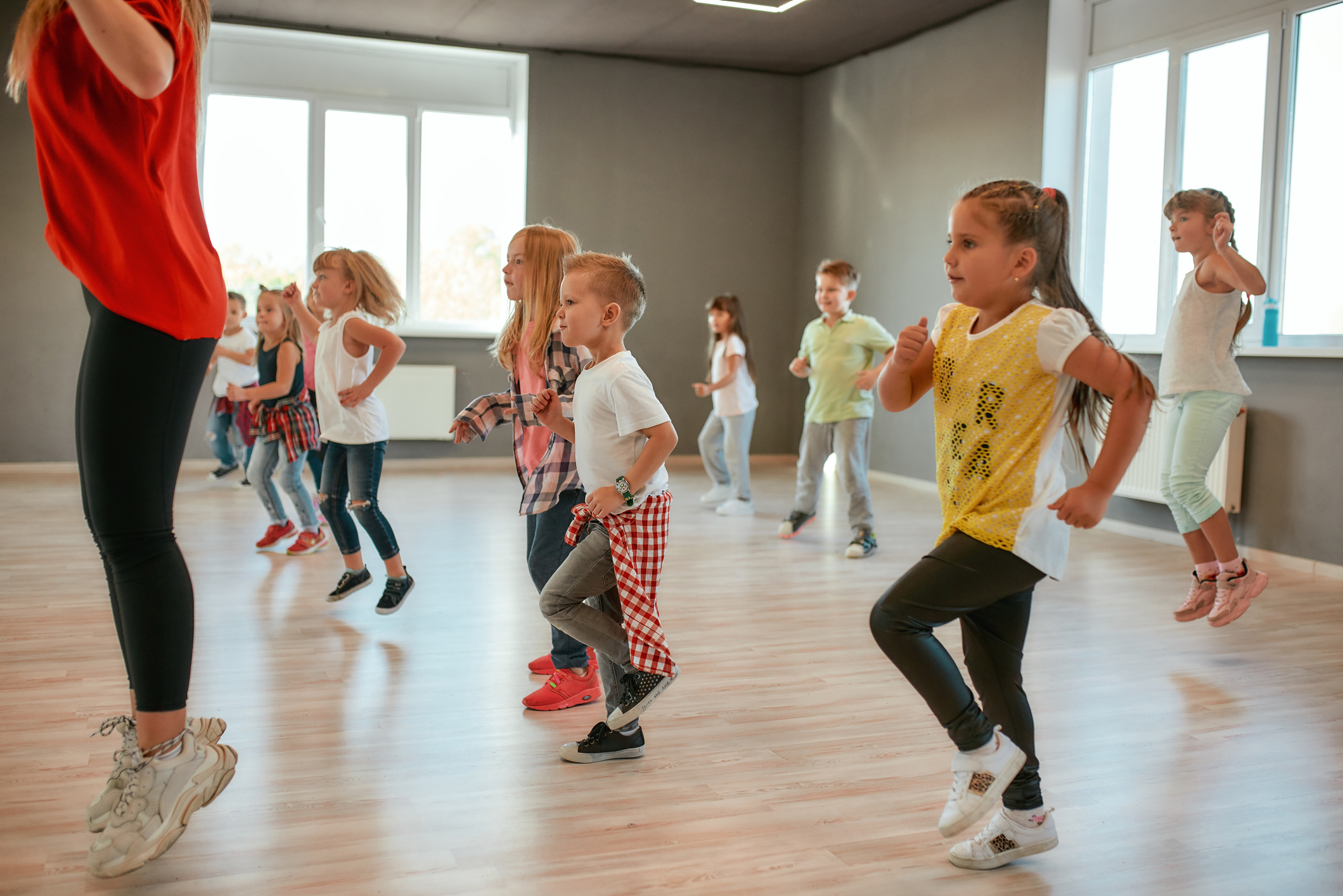 Group of little boys and girls dancing while having choreography class in the dance studio. Female dance teacher and children dancing. Contemp dance. Hip hop. Kids and sport. Full length