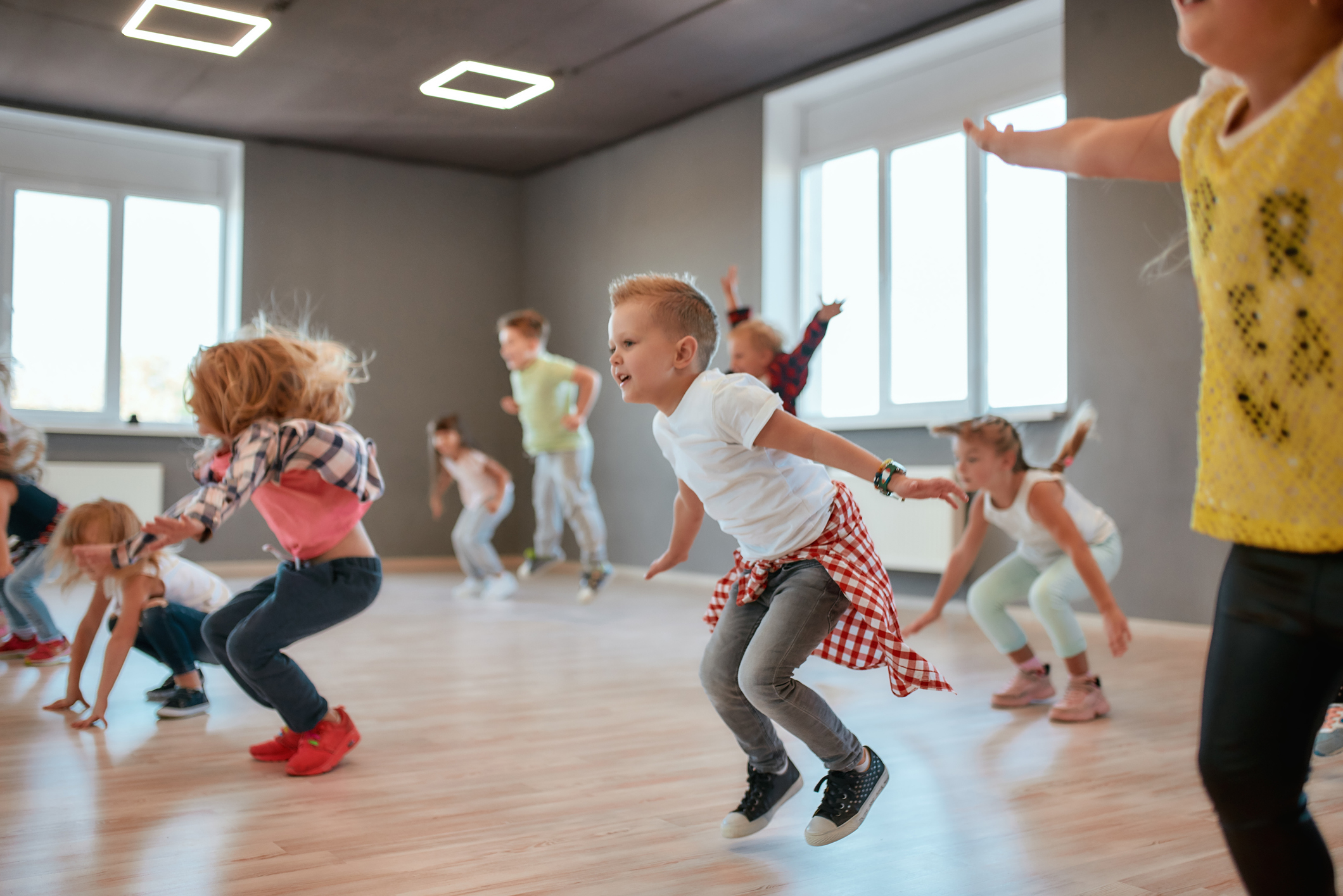 Group of cute little boys and girls studying modern dance in studio. Children jumping while having a choreography class. Sport. Active lifestyle